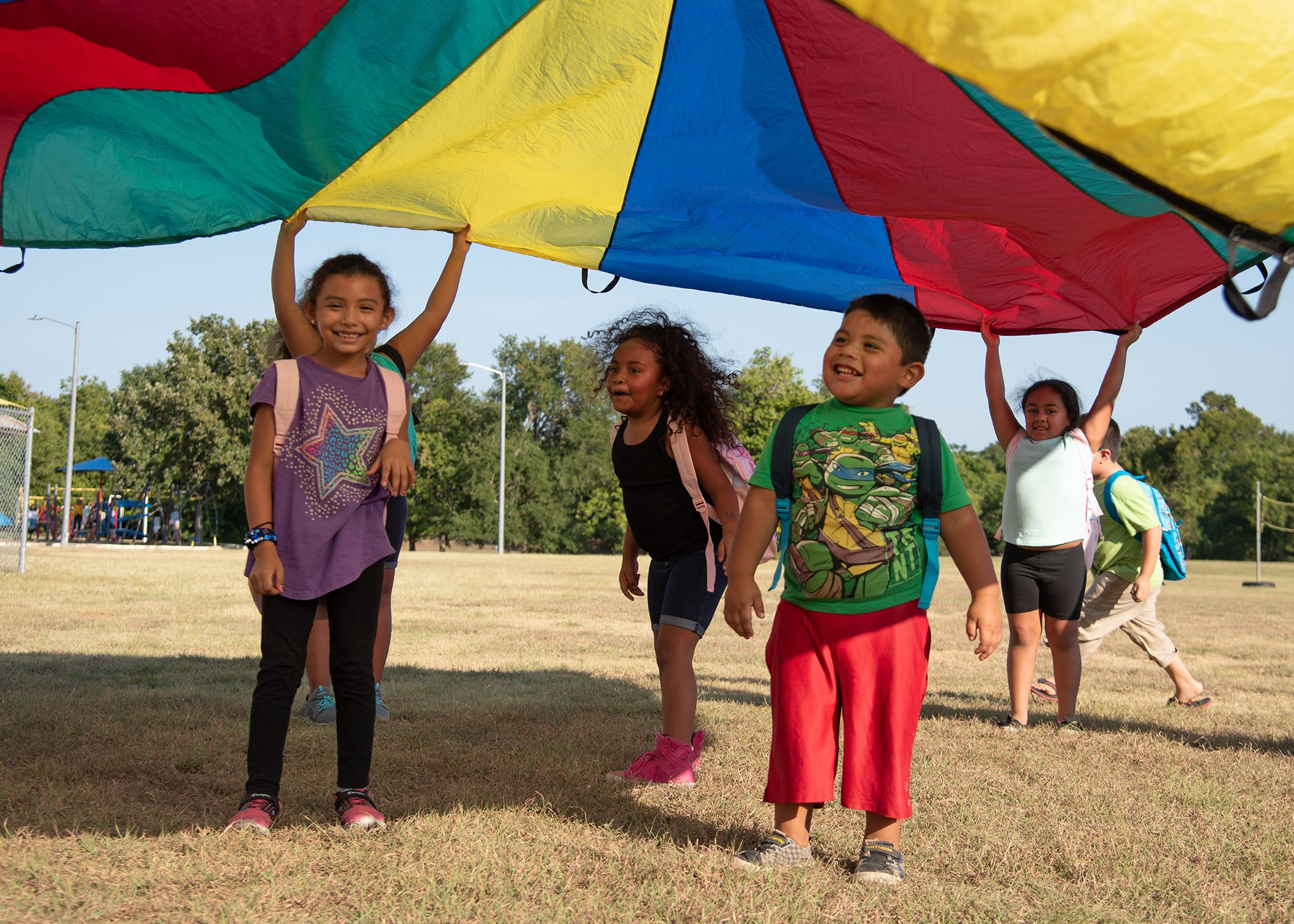 Photo of three kids playing under multi-color tent at Party in Your Park