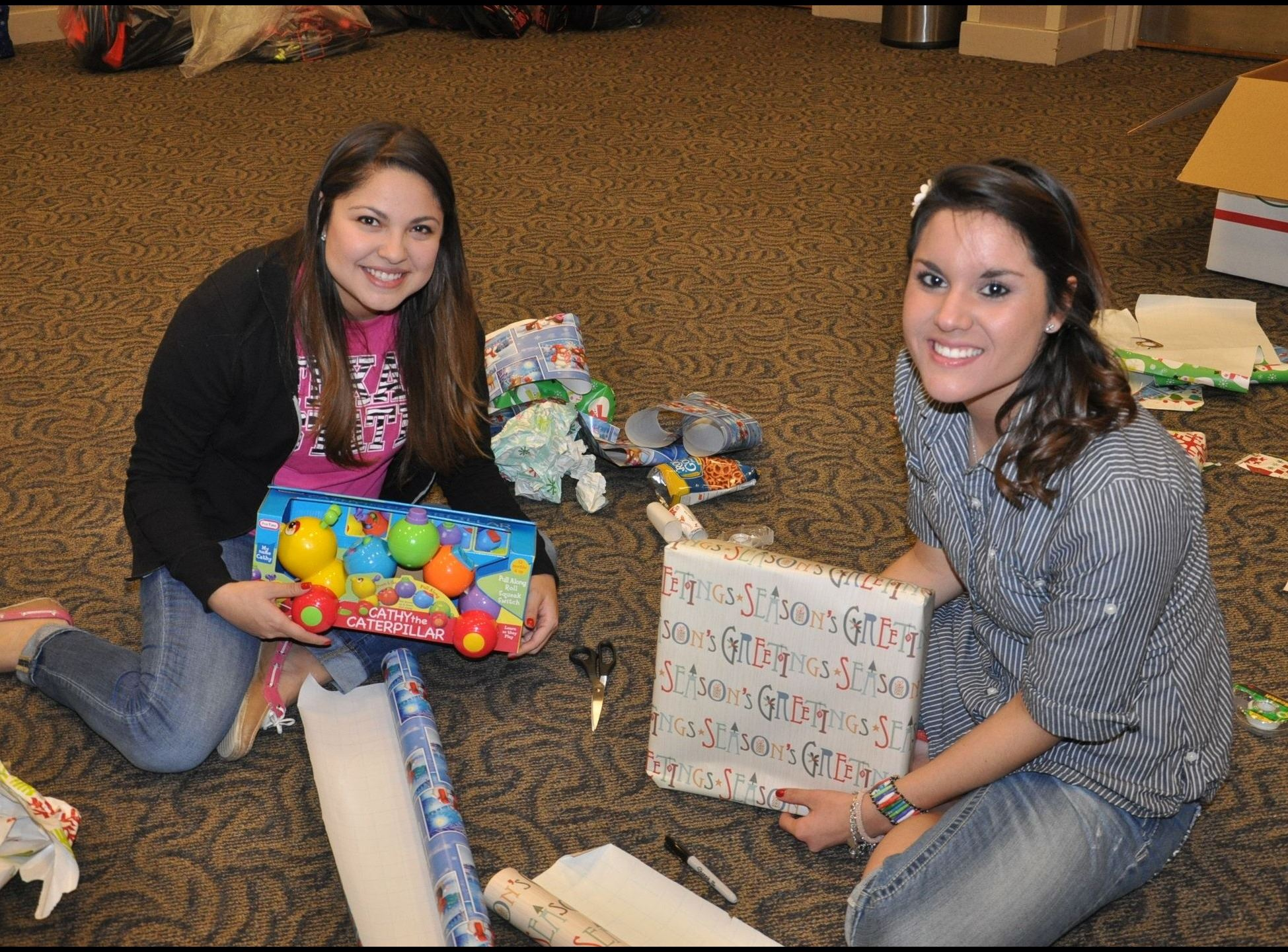 Photo of two women sitting on the ground wrapping gifts for the annual SMPD Blue Santa event.