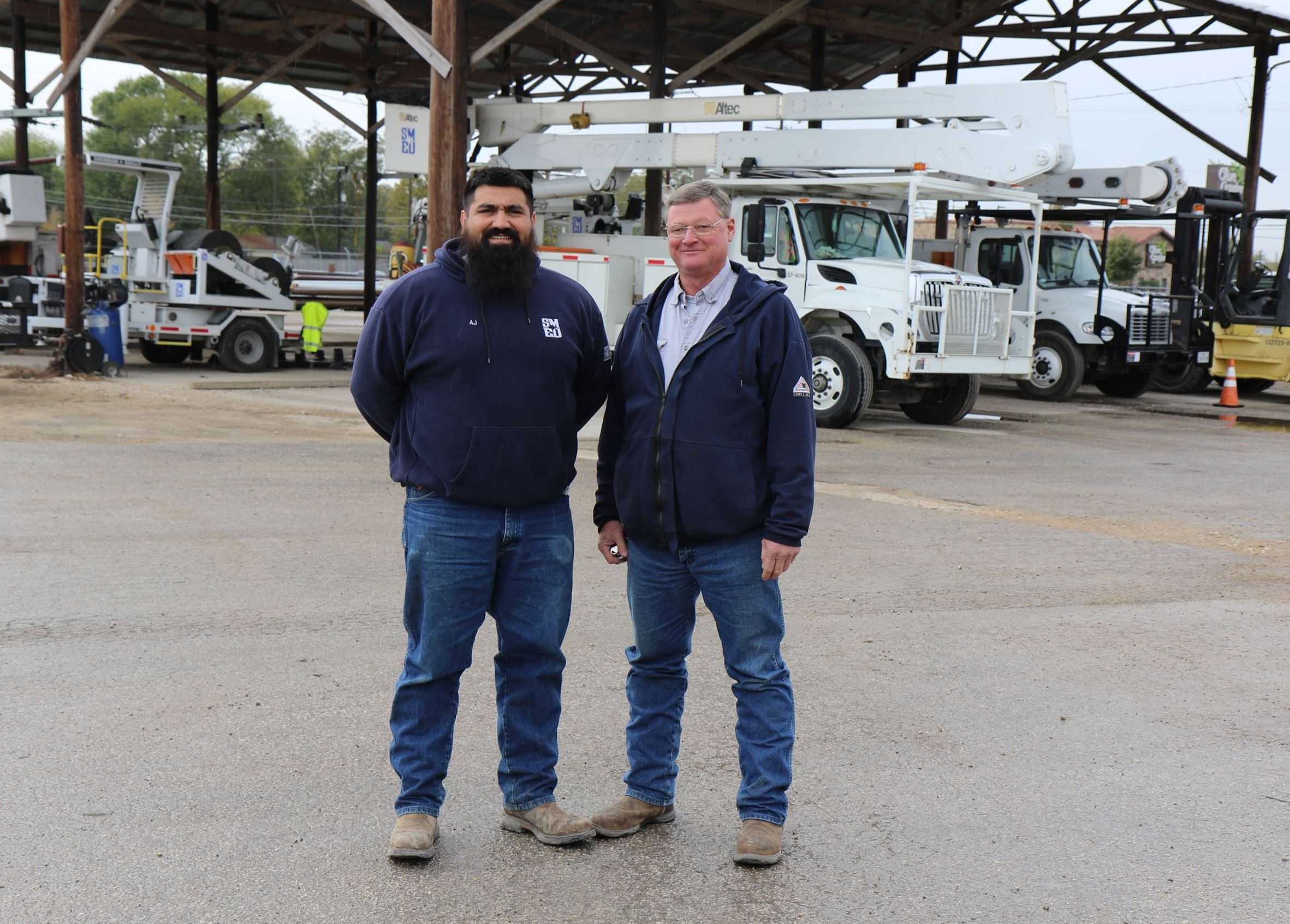 Photo of Longoria and Koehlers standing in lot of SMEU in front of utility vehicles