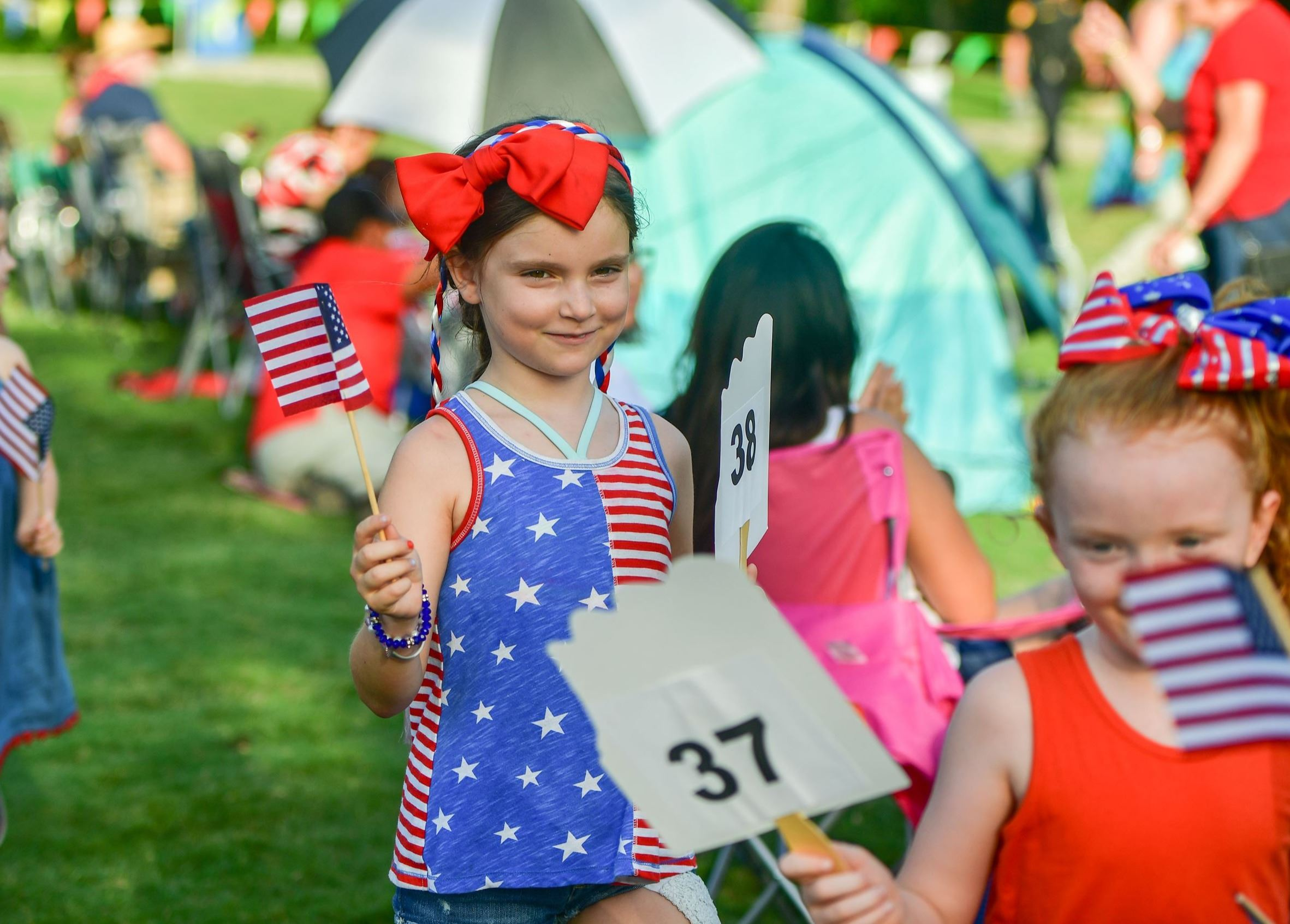 Photo of children standing in line wearing red, white, and blue outfits from previous SummerFest pat
