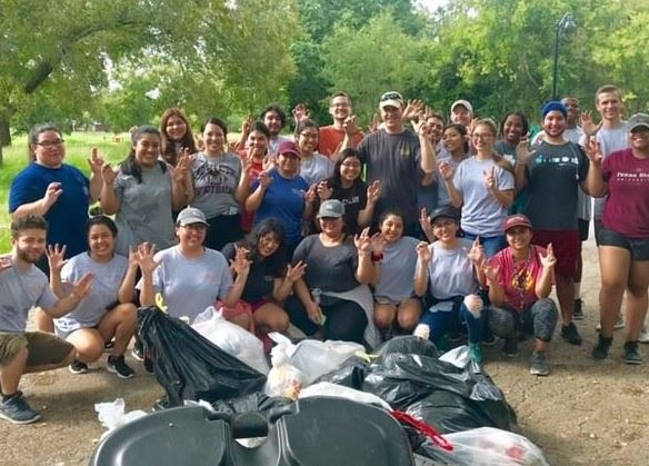 Photo of group of cleanup volunteers behind pile of collected trash at Willow Creek