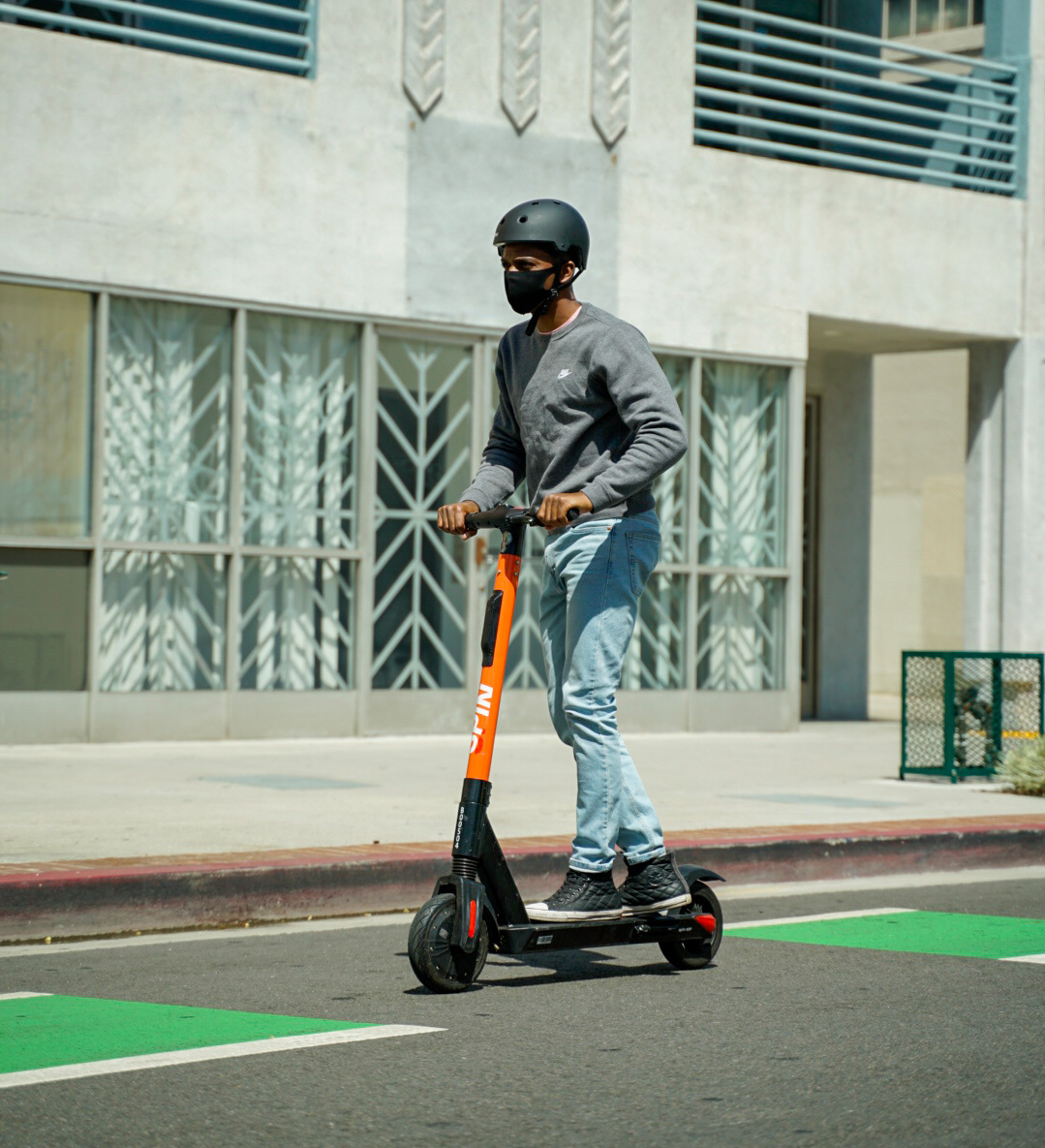 A person wearing a mask rides a scooter down the street