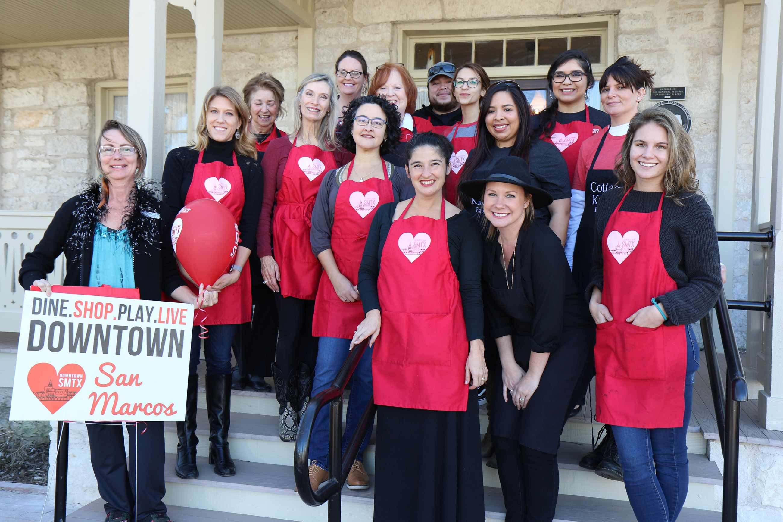 A dozen volunteers in red Main Street aprons standing on the steps of an old house