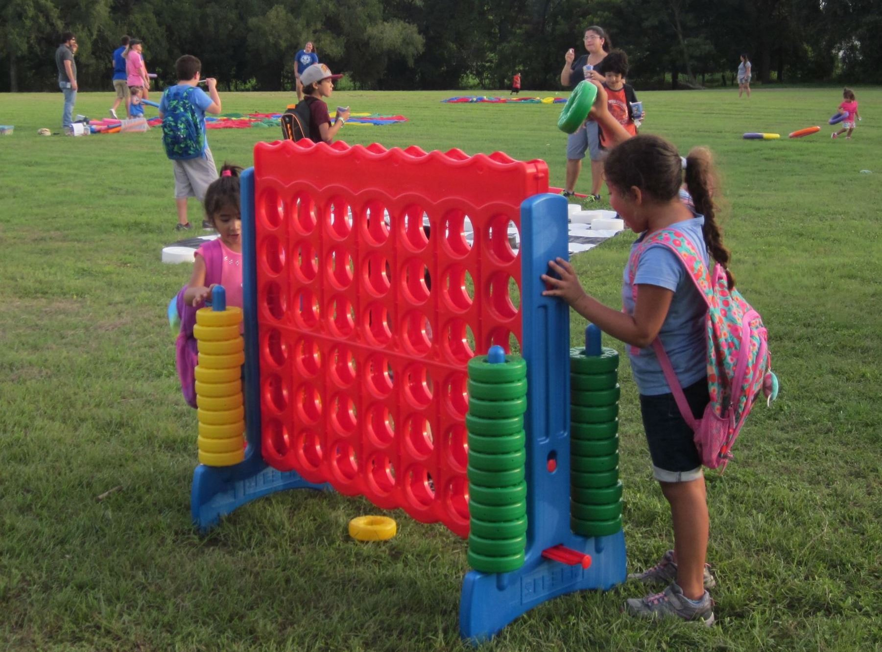 Children playing giant Connect 4 game at a park with families playing in the background