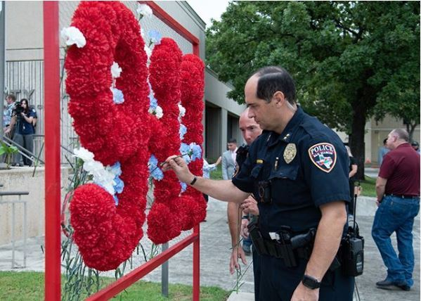 Photo of police officer placing a flower on 9/11 remembrance Flower Memorial