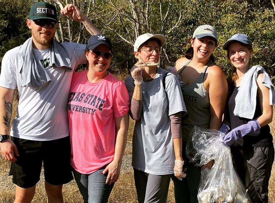 Volunteers posing with a bag of trash outdoors at the Purgatory Creek collection site