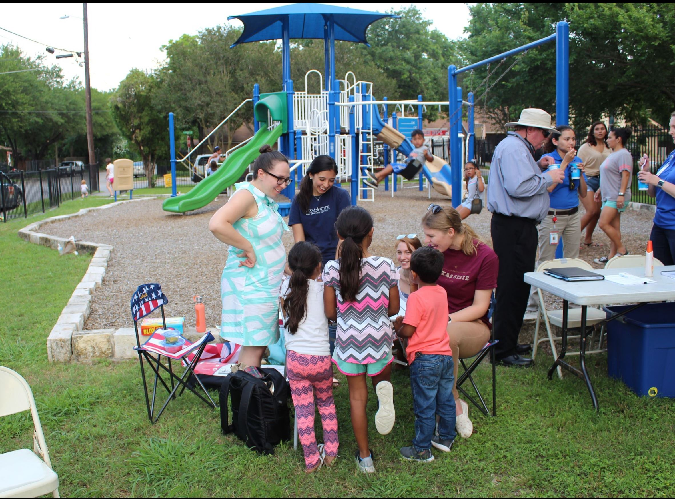 Photo of Texas State University students talking with local children at a park setting