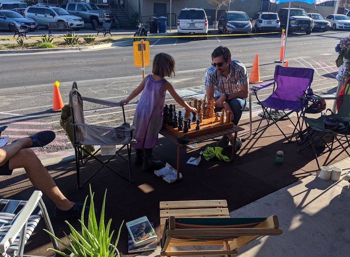 Photo from Downtown San Marcos Park(ing) Day 2019 featuring chess table in parking spot with two peo