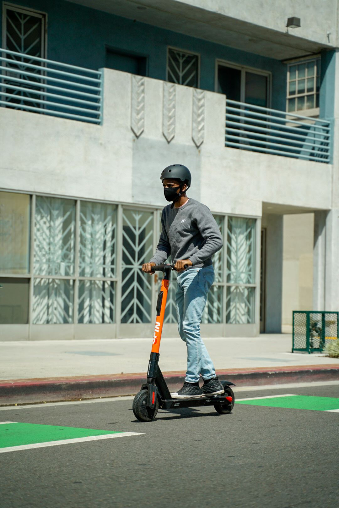 A young man rides a scooter down the street wearing a face mask